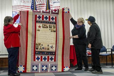 A quilt is awarded to a veteran during a Quilts of Valor ceremony at the Fayette County Extension office.   PHOTO: Carol Lea Spence