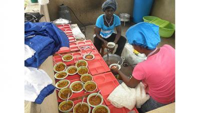 Female cooks serve food at the Kentucky Academy, a kindergarten in Adjeikrom, Ghana.