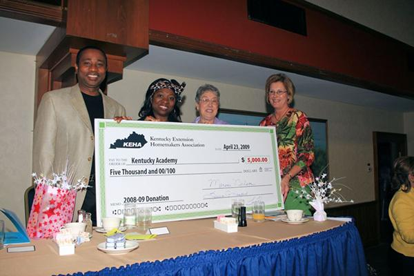 Kwaku and Esther Addo accept the ceremonial check for the Kentucky Extension Homemakers Association's first contribution to the Kentucky Academy from KEHA Leaders Jo Ann Ellegood and Linda Heflin.
