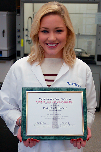 Katie Hahnel holding her Six Sigma Green Belt Certificate