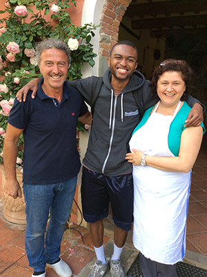 Jevincio Tooson is pictured with a family who hosted the students at their home and organic farm in Lucca, Italy.