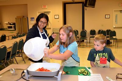Kendra Oo, UK dietetic intern, left, helps two participants with their stir fry recipe during Boyd County's Kids Can Cook.  PHOTO: Katie Pratt, UK Agricultural Communications