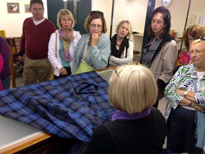 Examining plaid textiles at the House of Edgar warehouse