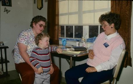 An archive photo of former Boyd County EFNEP  assistant Donna Powers working with a family.