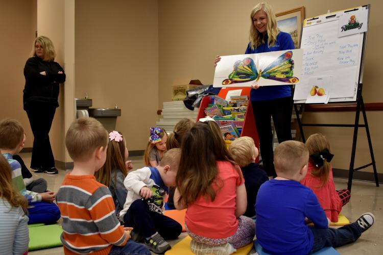 "Whitney Morrow, Carter County family and consumer sciences extension agent, reads ""The Very Hungry Caterpillar"" to young children attending her Play Date program at the extension office.."