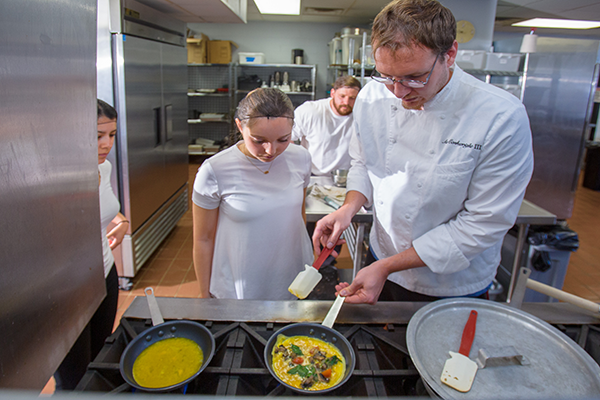 DHN students from the winning team (from left to right) Saleyka Calvillo, Alexis Scott, Bobby Powers and Asa Conkwright, teaching assistant for the class, prepare vegetable omelets from their restaurant menu for the judges to taste.